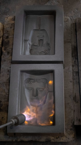 The sand casts are set on fire as they are prepared for the metal to be poured into them during the hand-made casting.