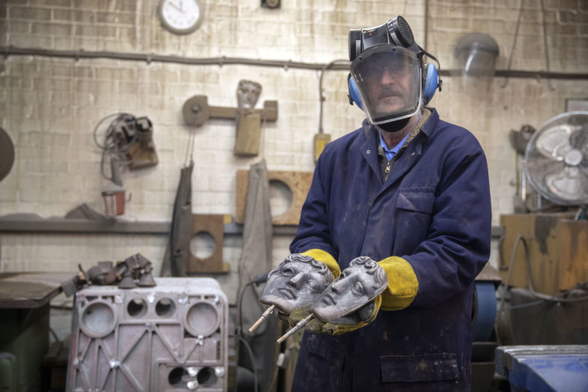 Patrick Helly holds two masks  during the hand-made casting.