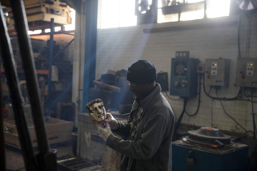 Rupert francis inspects a mask.