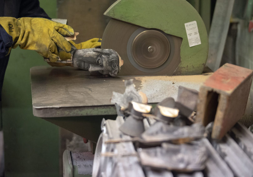 Patrick Helly grinds off the excess metal during the hand-made casting.