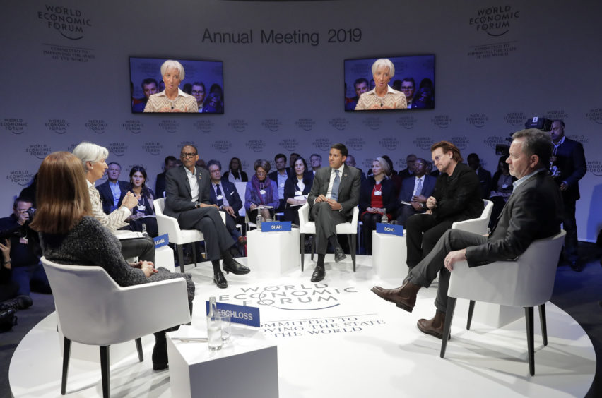 """Christine Lagarde, Managing Director of IMF, 2nd left, gestures to singer and co-founder of RED Bono, 2nd right, during the """"Closing the Financing Gap"""" session at the annual meeting of the World Economic Forum."""