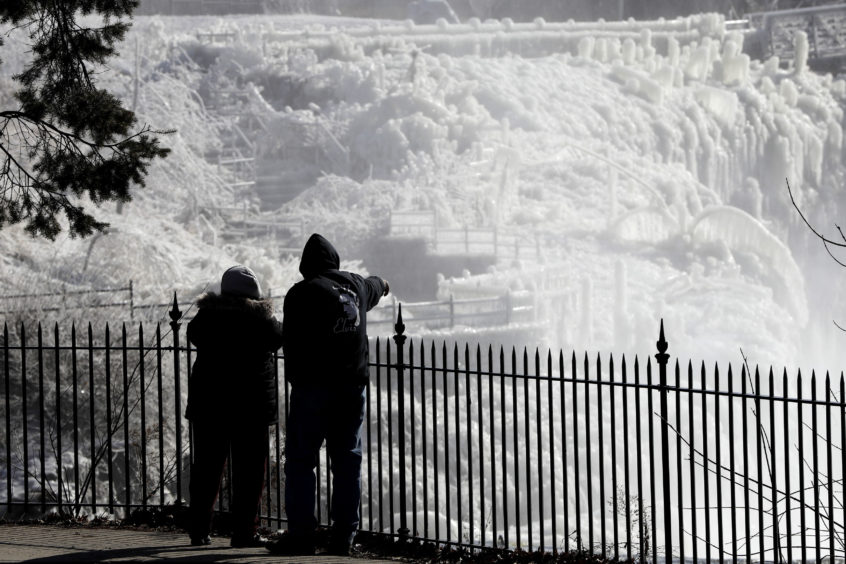Ice is seen on the side of the Great Falls National Historic Park as a couple takes in the sights during a frigid winter day in Paterson, N.J. The cold snap followed a snowstorm and snow squalls are expected in the afternoon before temperatures continue to dip below the freezing point.