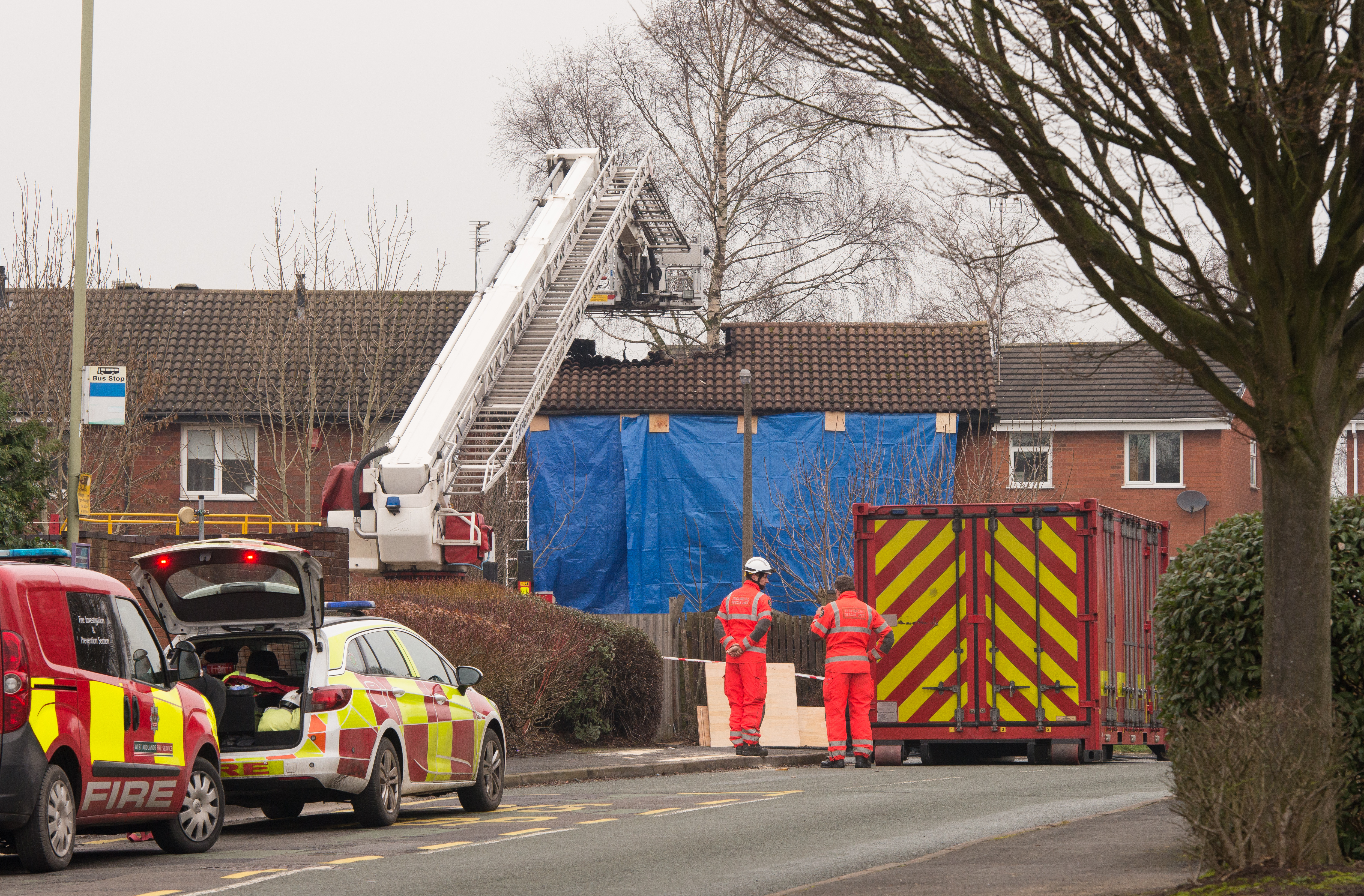 Staffordshire Fire and Rescue personnel stand outside a tarpaulin covered property with a burnt out roof at the scene of a deadly house fire on February 5, 2019 in Stafford, England.