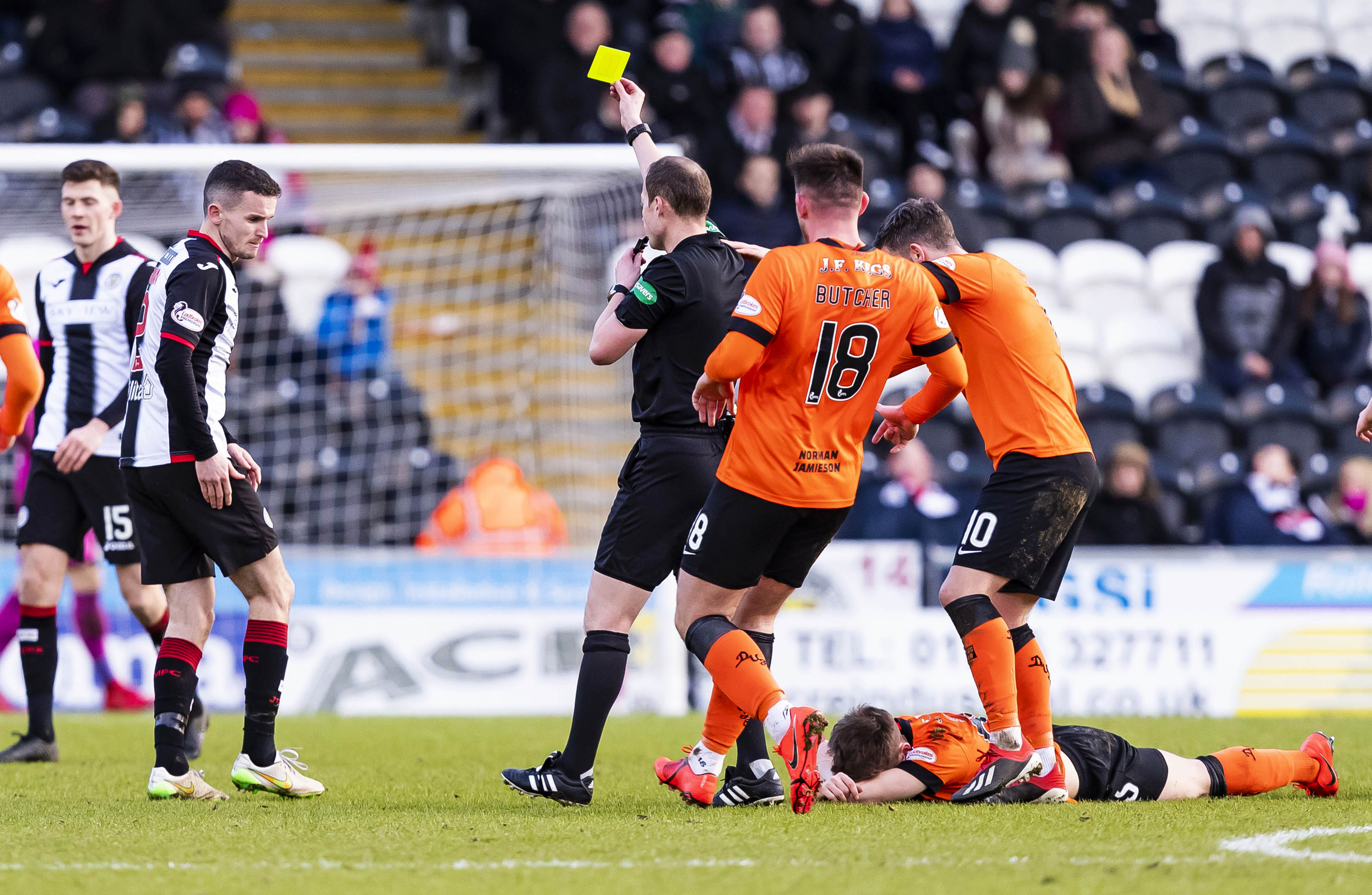 St Mirren's Paul McGinn (L) is booked by Willie Collum (centre) after clashing with Dundee United's Cammy Smith (on ground).