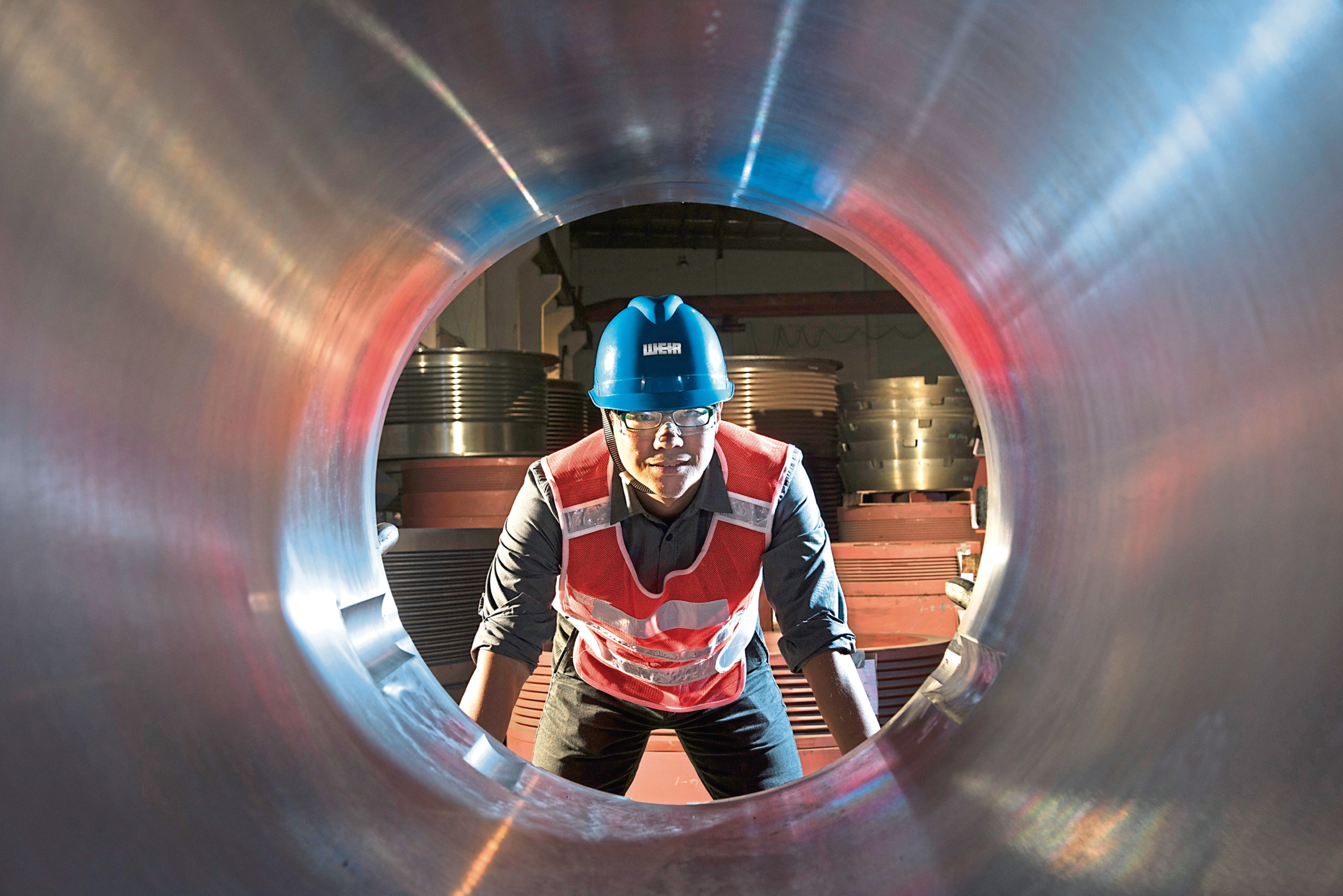 A Weir Group worker inspects a steel pipe