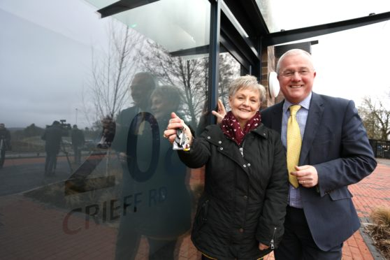 Resident Angela Grainger with housing and communities convener Peter Barrett and the keys to her new flat.