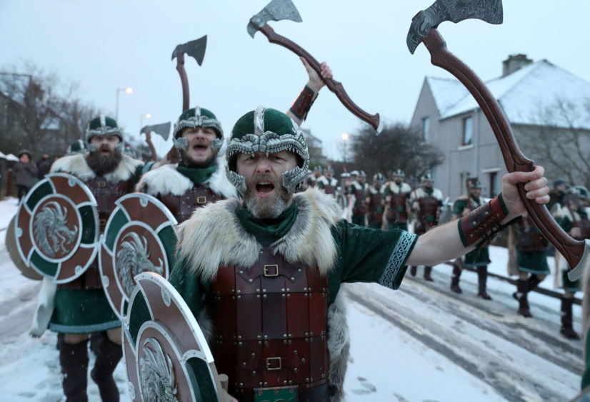 Members of the Jarl Squad cheers as they march through Lerwick as snow falls on the Shetland Isles during the Up Helly Aa Viking festival.