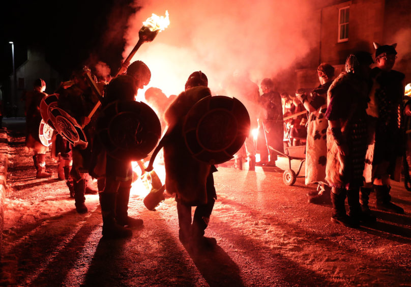 A flare is fired to light the torches of the Jarl Squad as they march through Lerwick ahead of the Galley being set on fire on Shetland Isles during the Up Helly Aa Viking festival.