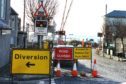 Work has begun on the Carnoustie level crossing which has closed Station Road.