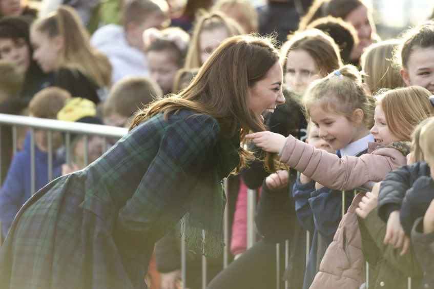 Kate lets a girl touch her hair as she meets school children outside a community centre in Dundee.