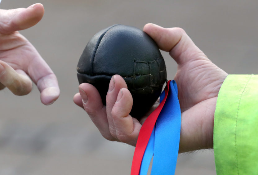The leather ball is held during the annual 'FasternÕs E'en Hand Ba' event on Jedburgh's High Street in the Scottish Borders.