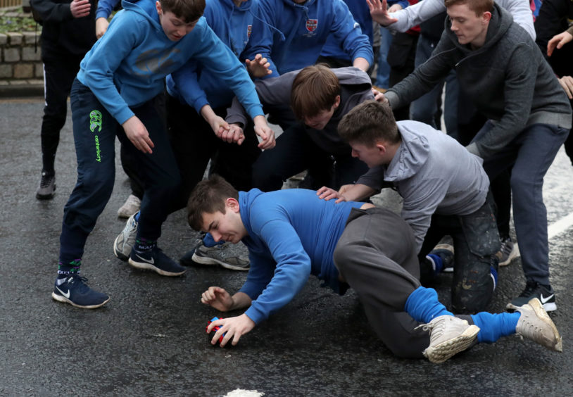 Boys dive on the leather ball during the annual 'FasternÕs E'en Hand Ba' event on Jedburgh's High Street in the Scottish Borders