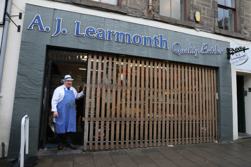 Butcher Bill Liddle looks out from his shop ahead of the annual 'FasternÕs E'en Hand Ba' event on Jedburgh's High Street in the Scottish Borders.