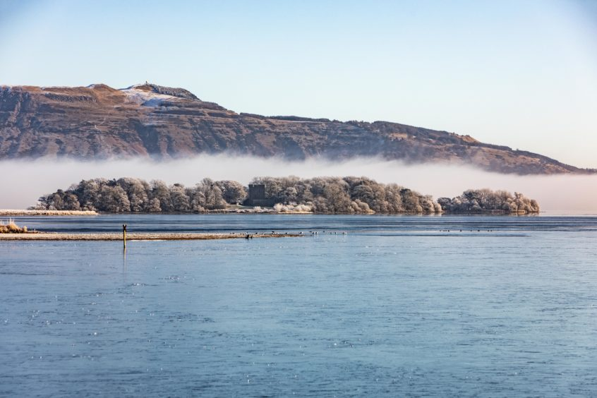 Loch Leven Castle emerges from the freezing fog on its island within Loch Leven in Fife.