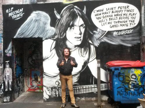 Ben Scott pictured next to Malcolm Young graffiti in AC/DC Lane in Melbourne, Australia