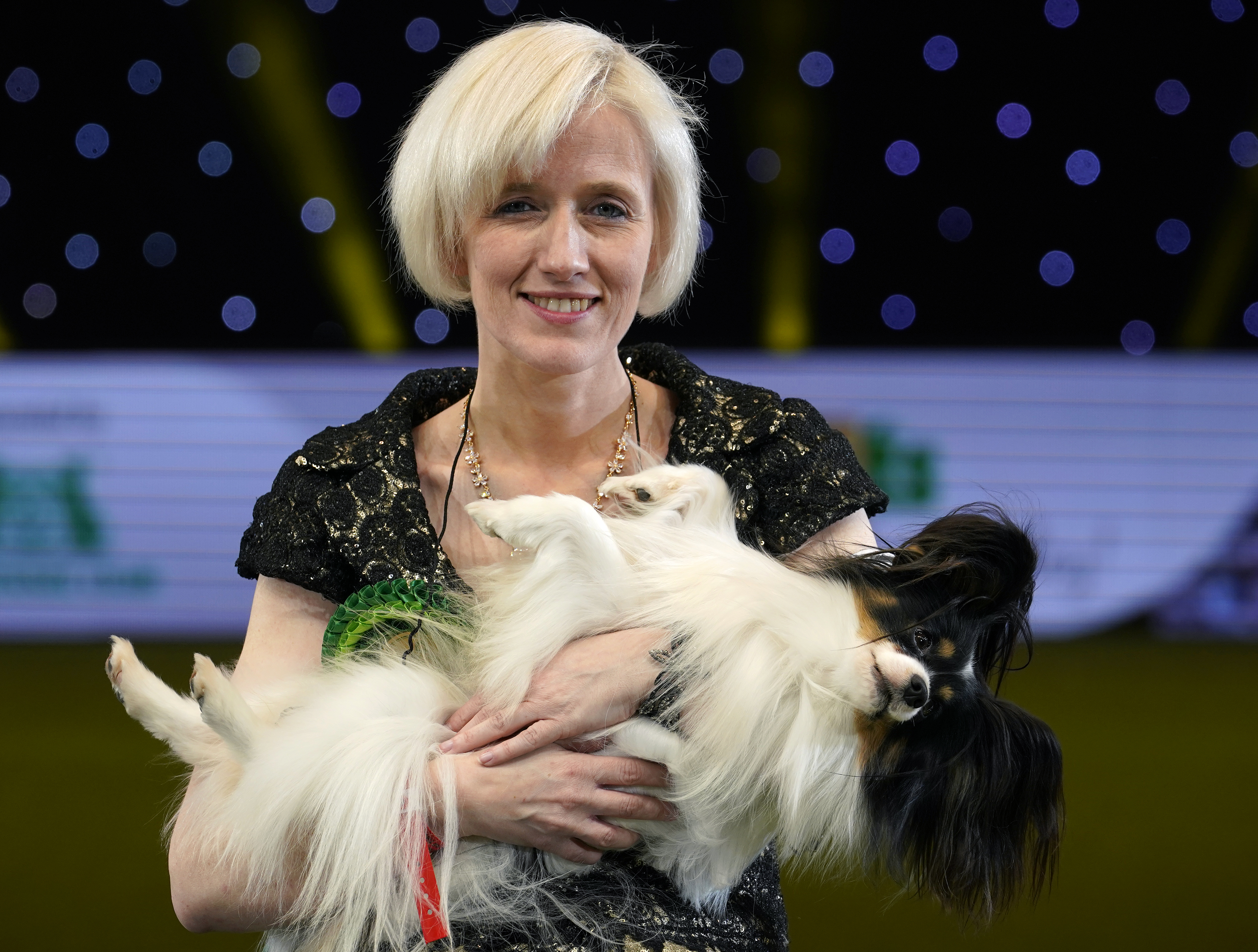 Dylan, a Papillon from Belgium, and owner Kathleen Roosens celebrate after winning Best in Show on the last day of Crufts Dog Show at the National Exhibition Centre on March 10, 2019 in Birmingham, England. .