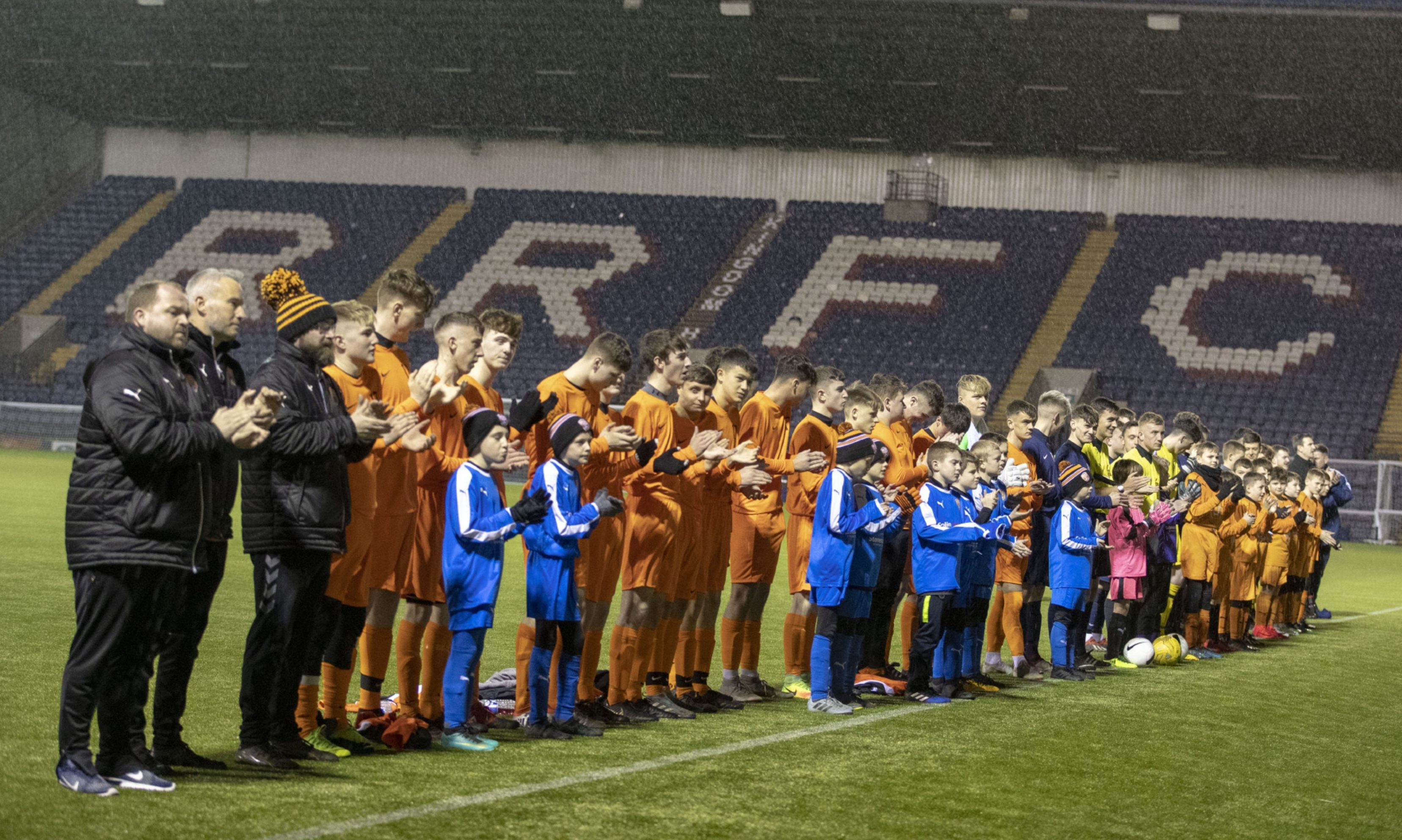 Both teams and officials join friends and family in the minute's applause ahead of the game.