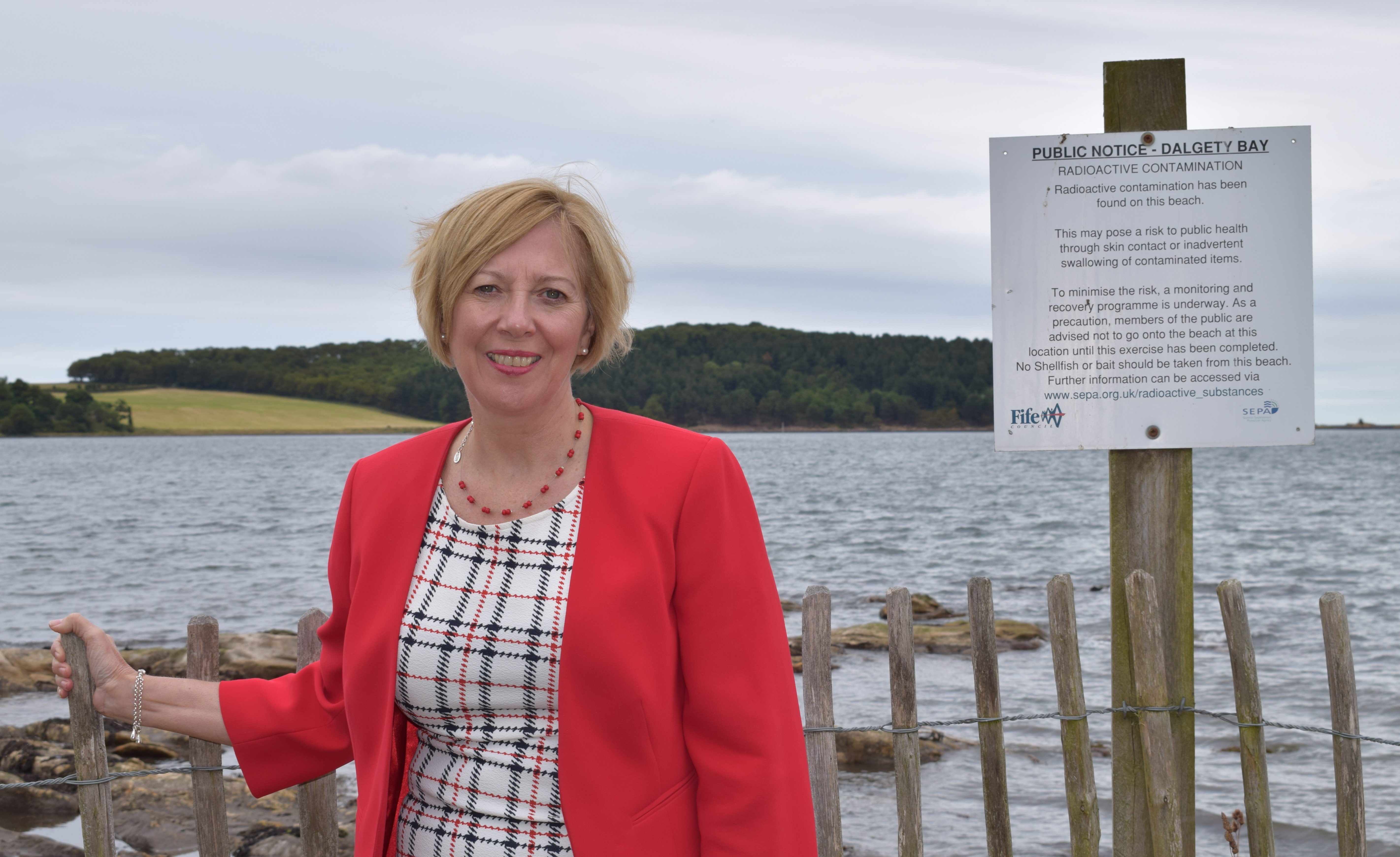 Mrs Laird at the warning sign on the foreshore