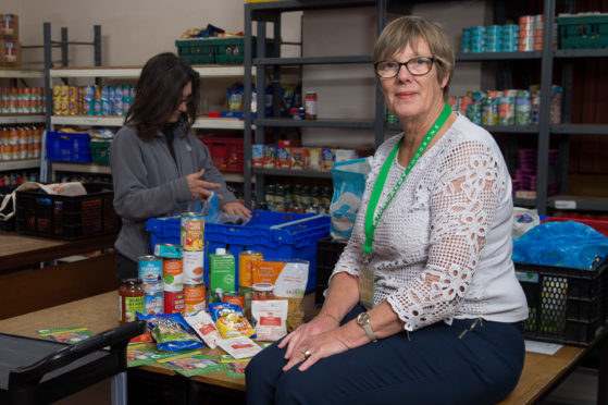 Joyce Leggate, chairman of the foodbank with a typical three day emergency food parcel for a single person in 2019