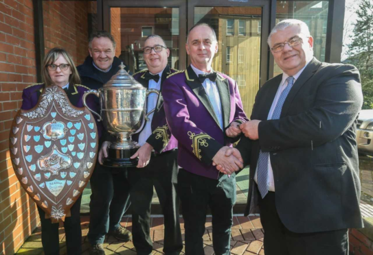 Councillor Gary Guichan hands over the keys to William Mclaughlin of Kingdom Brass, watched by Michelle McLaughlin, Councillor Alex Campbell and Paul Hamilton.