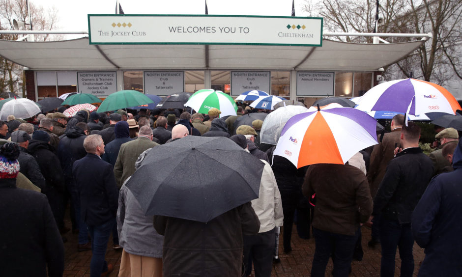 Racegoers shelter from the rain as they wait for the gates to open. Andrew Matthews/PA