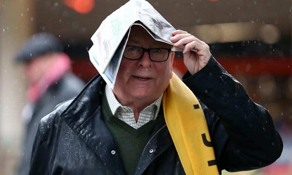 A racegoer shelters from the rain. Nigel French/PA