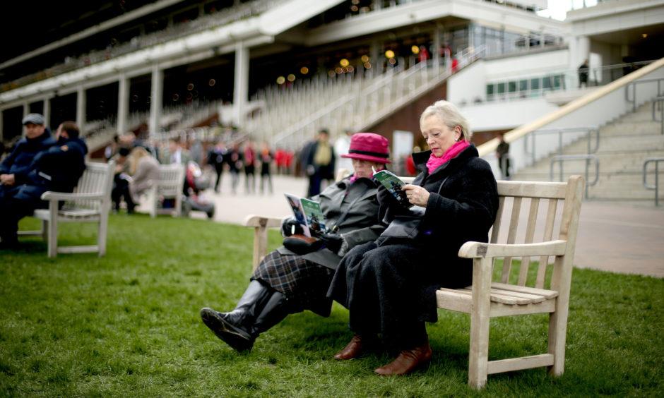 A racegoer reads a programme. Paul Harding/PA