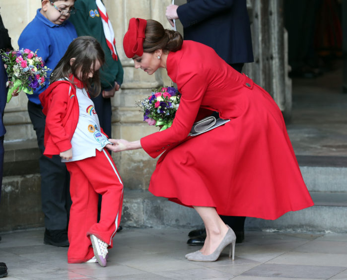 A young girl presents the Duchess of Cambridge with a bouquet of flowers.