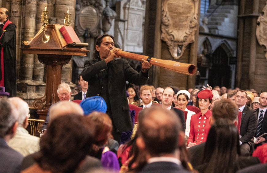 International didgeridoo player William Barton performs in the aisle at the Commonwealth Service at Westminster Abbey.