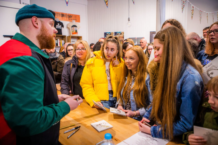 Tom chats to fans (left to right) Freya Vannet (aged 15), Charley Warden (aged 15) and Elise Duffy (aged 15). Assai Records.