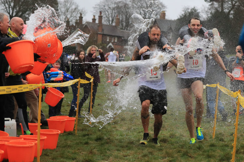Competitors have water thrown at them as they take part in the annual UK Wife Carrying Race at The Nower in Dorking, Surrey.