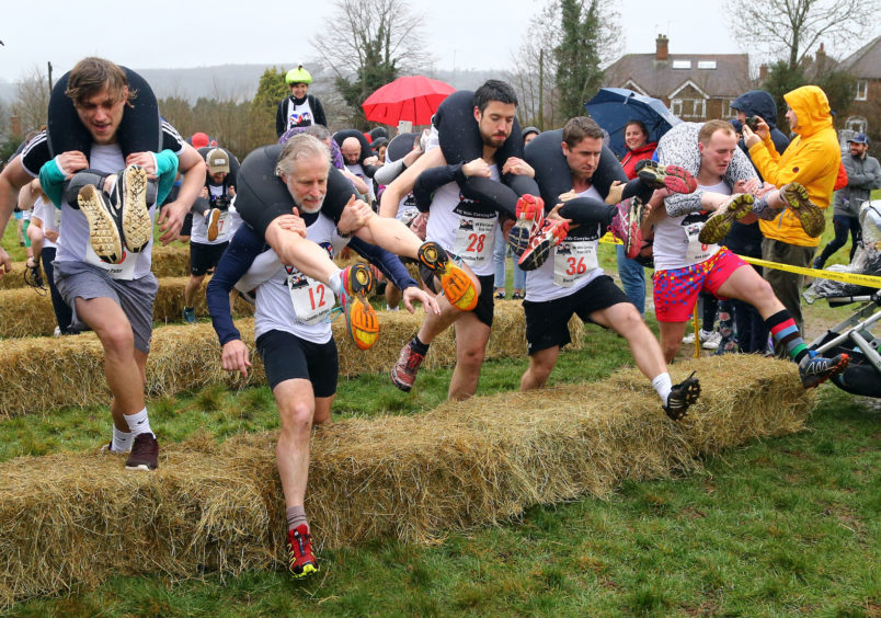 Competitors take part in the annual UK Wife Carrying Race at The Nower in Dorking, Surrey.