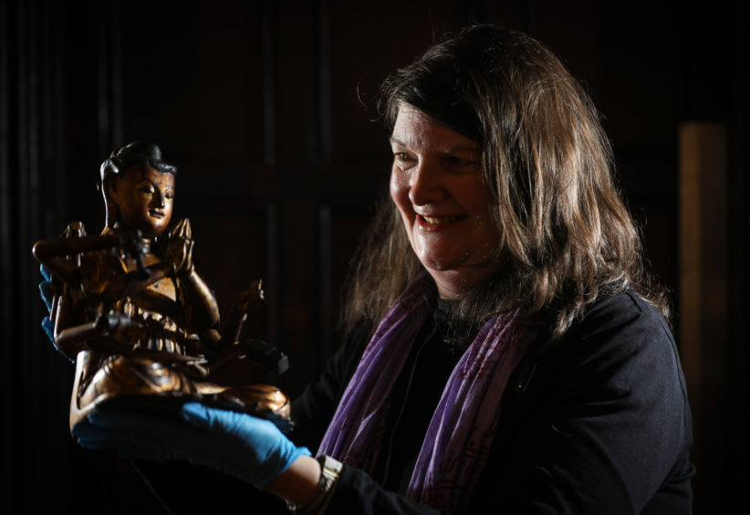 Christina Donald, curator of early history with an altar figure of Guanyin