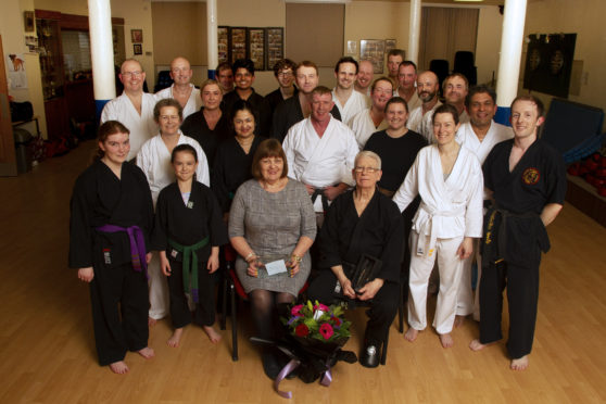 Karate black belt Jim Fraser and his wife Dorothy with Alex Sloan (centre) at the presentation