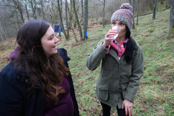 Gayle Ritchie enjoys birch water fresh from the tree while Gabrielle Clamp of Birken Tree looks on.