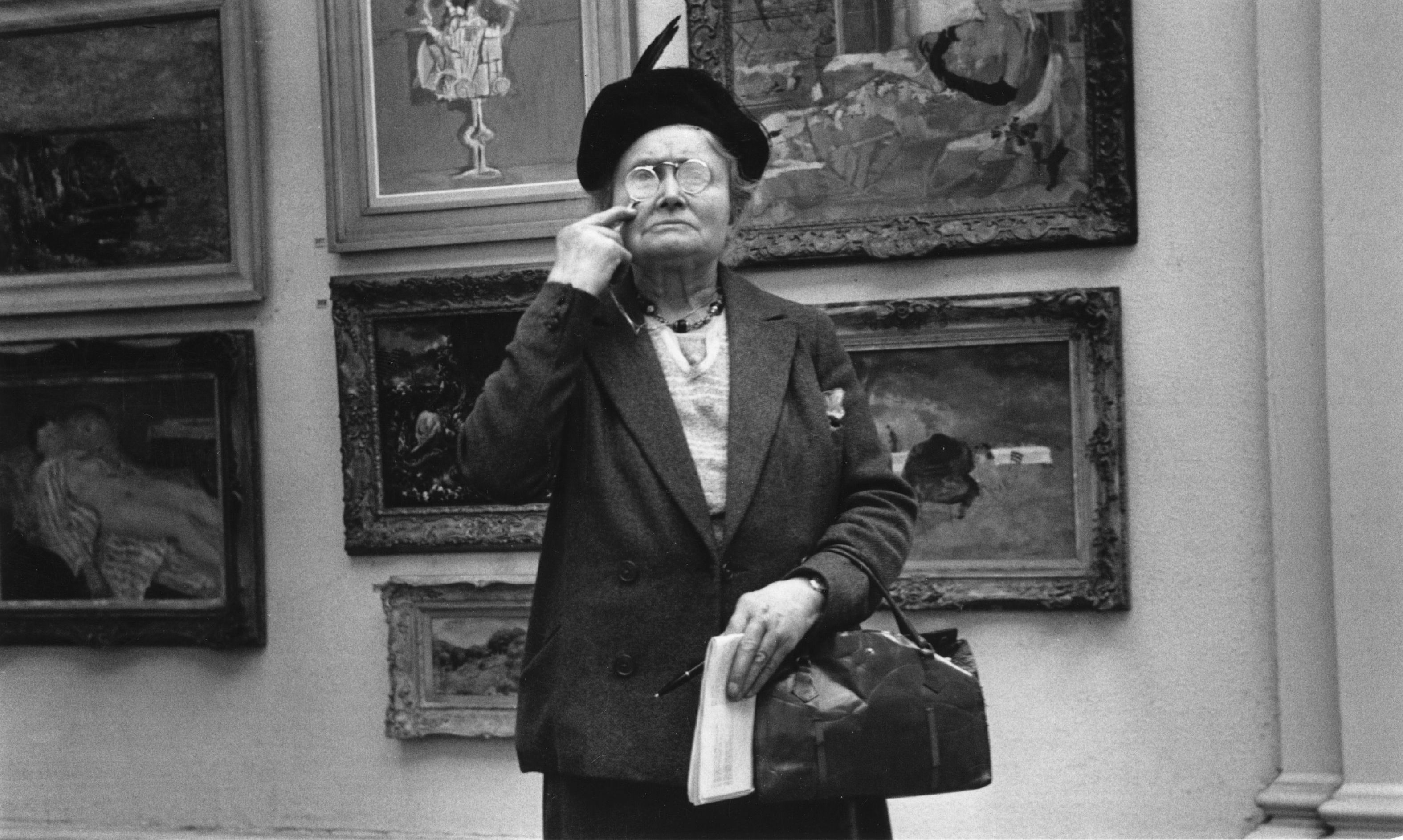 An elderly woman peers at a painting through a magnifying glass at the Tate Gallery, London. Original Publication: Picture Post