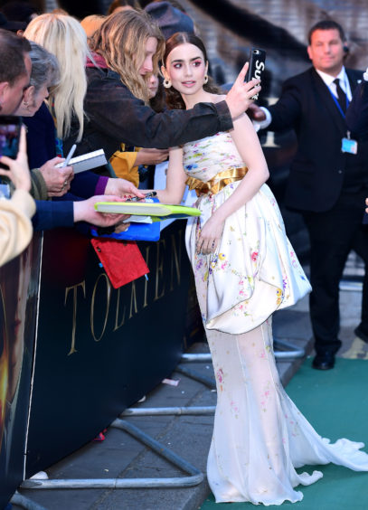 Lily Collins poses for photographs during the UK premiere of Tolkien held at Curzon Mayfair, London .