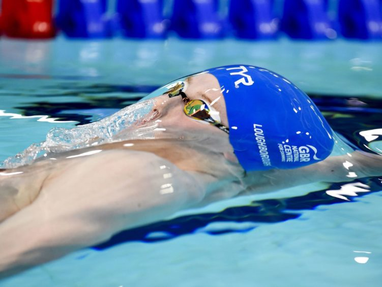 Joe Litchfield on his way to winning his heat of the Mens 100m Backstroke.