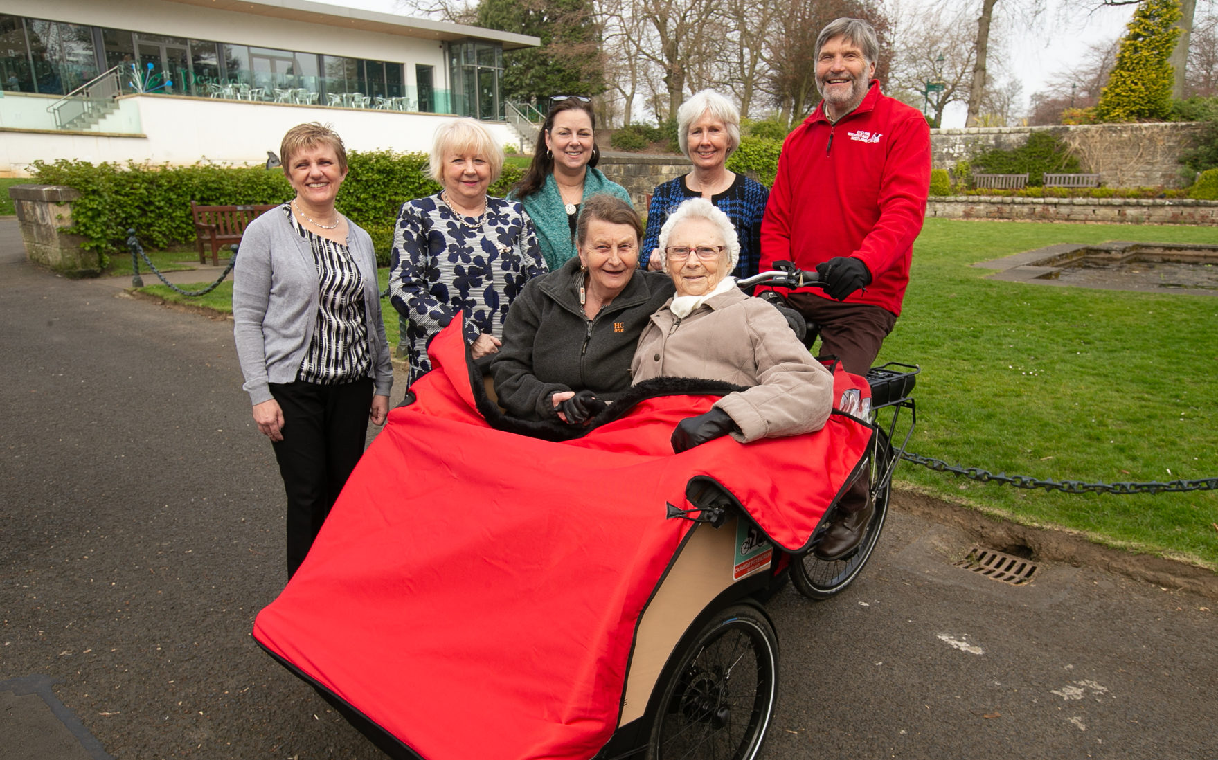 Residents of The Beeches Care Home try out the trishaws in Pittencrieff Park.  Group pic includes Cllrs Judy Hamilton, Helen Law and Jean Hall Muir alongside Ruth Ray (Trustee and Sports Convener for Carnegie Dunfermline Trust) and volunteer Frank Waterworth.