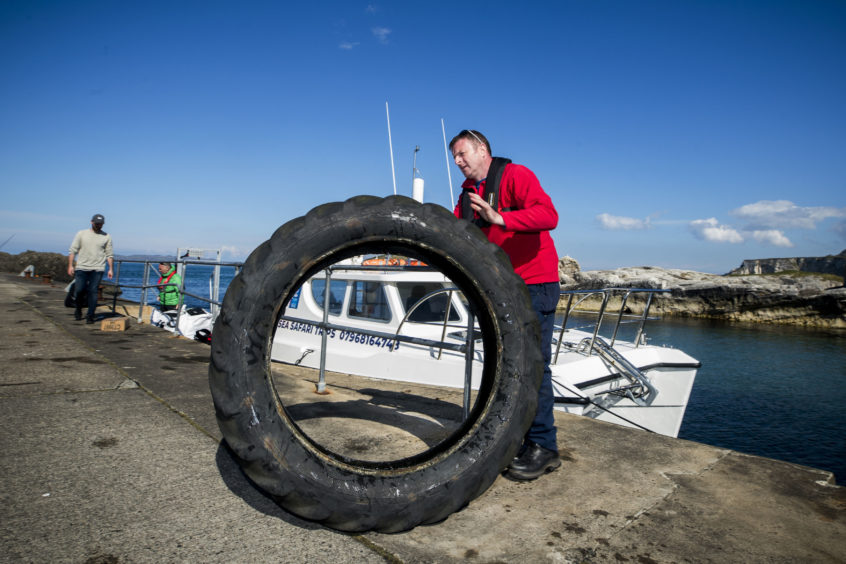 A member of the National Trust  with a tractor tyre at Ballintoy Harbour during a litter pick around the coastline of the Giant's Causeway in Northern Ireland.