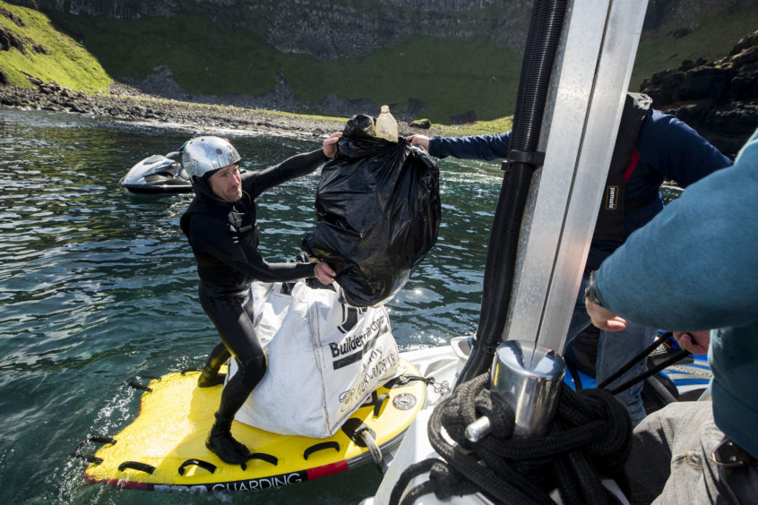 Volunteers load rubbish onto a boat during a litter pick around the coastline of the Giant's Causeway in Northern Ireland.
