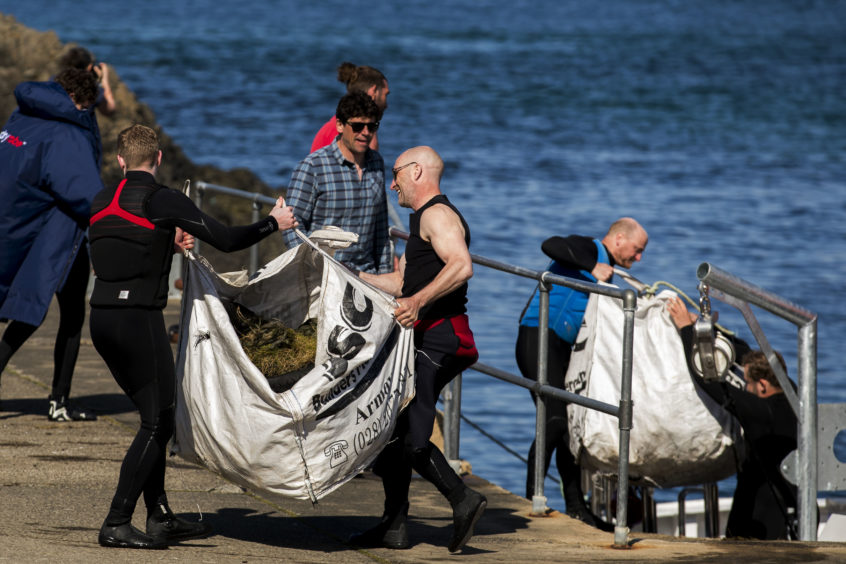 Volunteers haul rubbish from the Causeway Maid boat onto the dock at Ballintoy Harbour during a litter pick around the coastline of the Giant's Causeway in Northern Ireland.