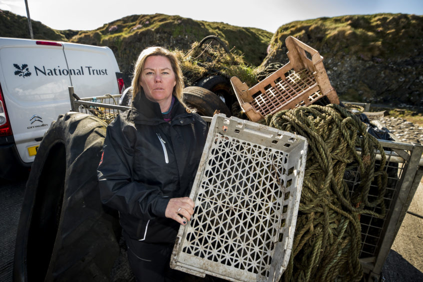 Coastal officer for the National Trust in Northern Ireland Fiona Bryant, stands with some of the items found during a litter pick around the coastline of the Giant's Causeway in Northern Ireland.
