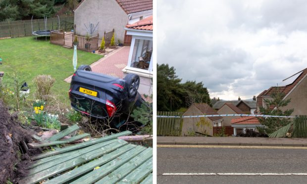 A black Ford Fiesta lies on its roof in a garden a few feet from a conservatory in Kinross after an accident.