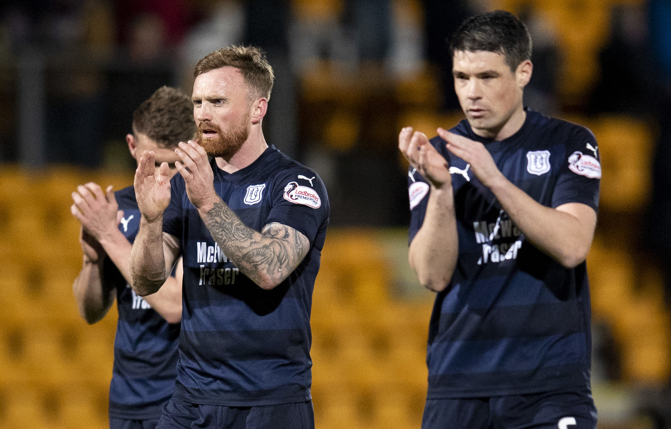 The Dundee players applaud their fans at full-time.