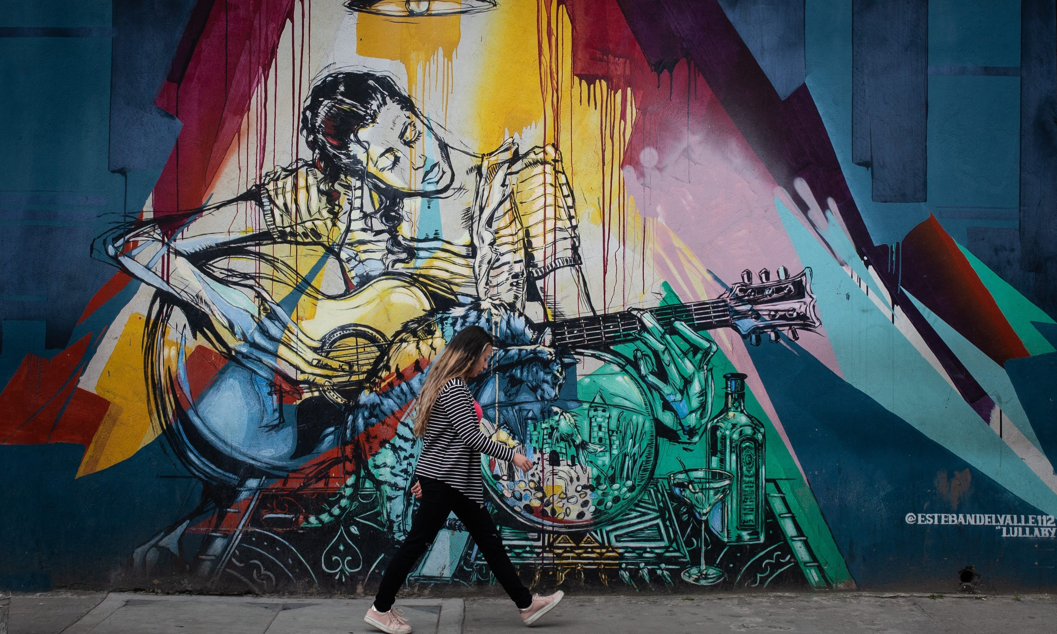 Person walks in front of a wall with graffiti in Bogota.