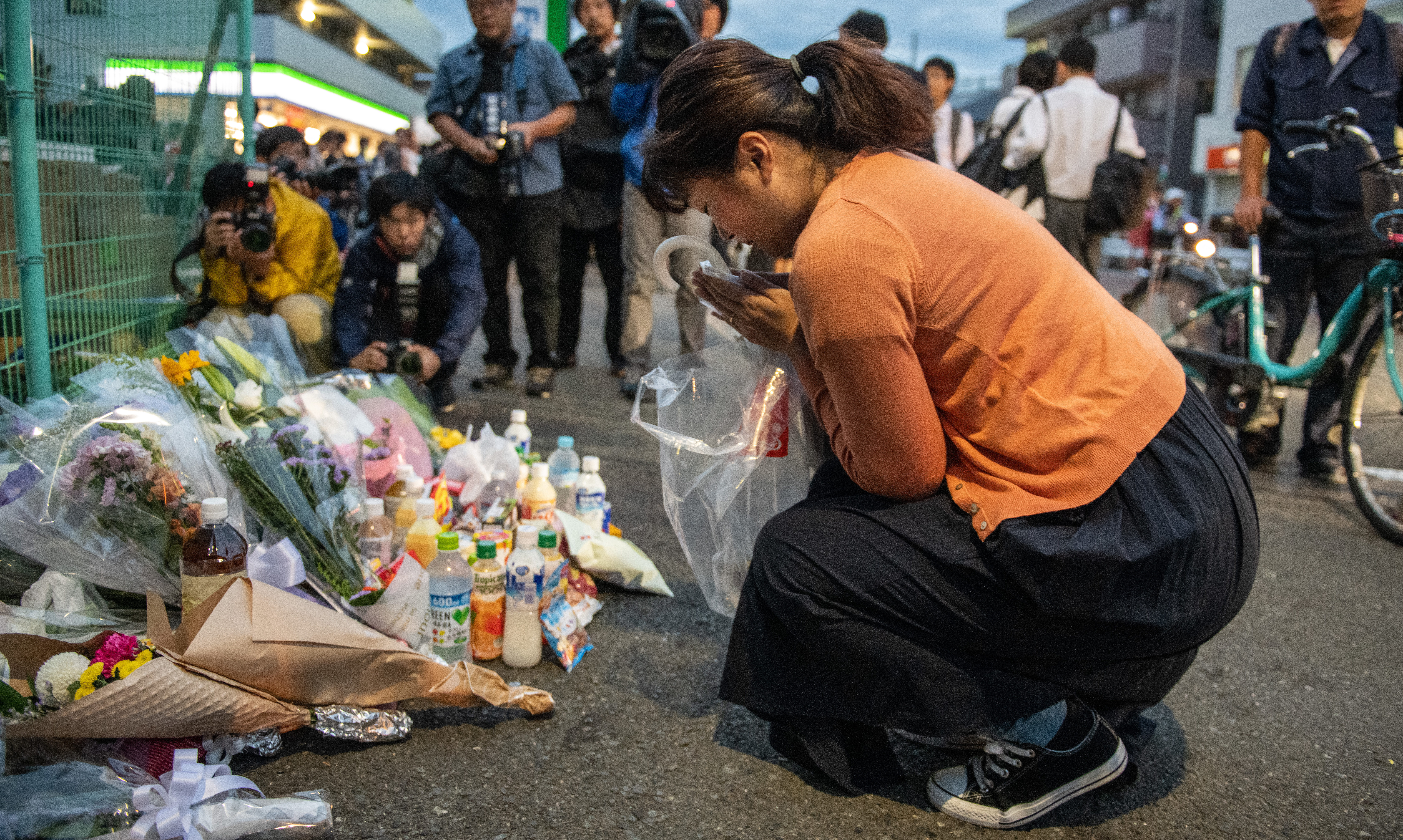 A woman prays at the scene of a knife attack on a group of schoolchildren.