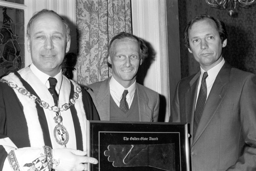 1985 of Master of the Worshipful Company of Glovers Stephen Kirsch (left) presents the Golden Glove Award to McLaren Formula One team boss Ron Dennis (right) and his driver Niki Lauda.