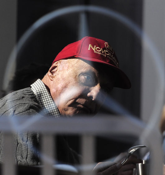 Former Austrian Formula One driver Niki Lauda is pictured through a glass window, during the 2015 Formula One testing, at the Barcelona Catalunya racetrack in Montmelo, Spain.