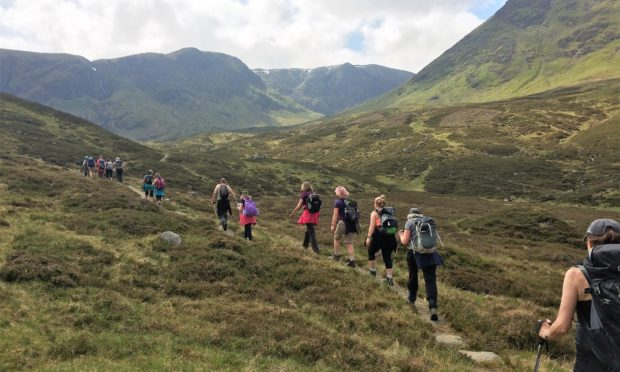 A group of walkers enjoying the tranquil peace of the Angus Glens.